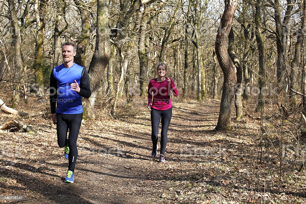 Mature couple running in forest royalty-free stock photo