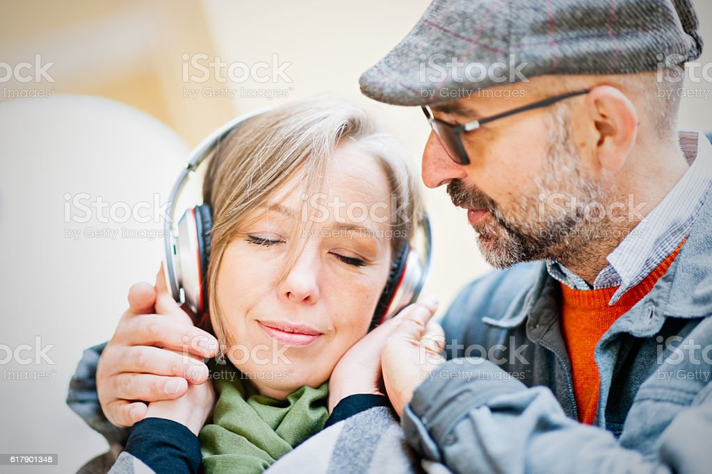 Mature couple share a music by headphones stock photo