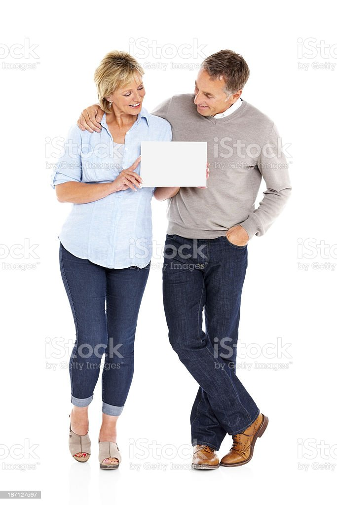 Mature couple showing empty billboard on white royalty-free stock photo