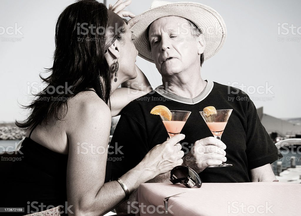 Mature Couple Sipping Flirtinis By The Sea royalty-free stock photo