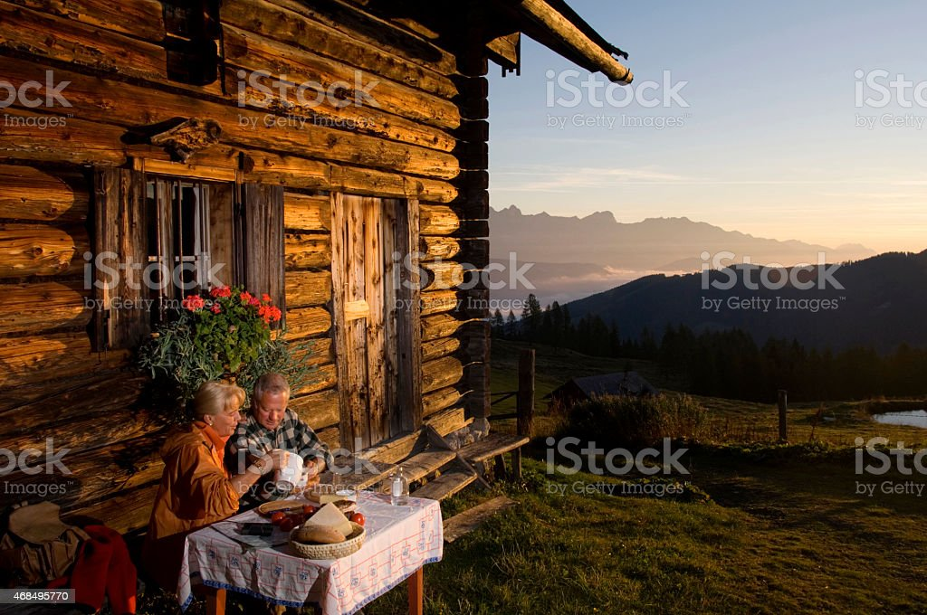 Mature couple sitting in front of alpine hut, watching sunset stock photo