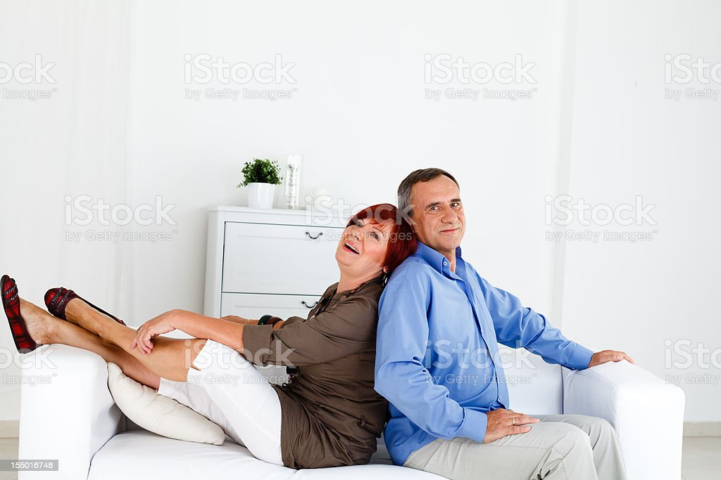 Mature Couple Sitting on a Couch and Smiling royalty-free stock photo