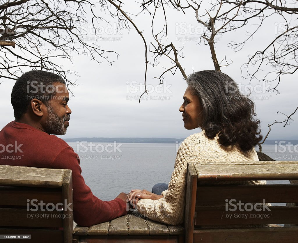 Mature couple sitting on bench by sea, smiling, rear view royalty-free stock photo