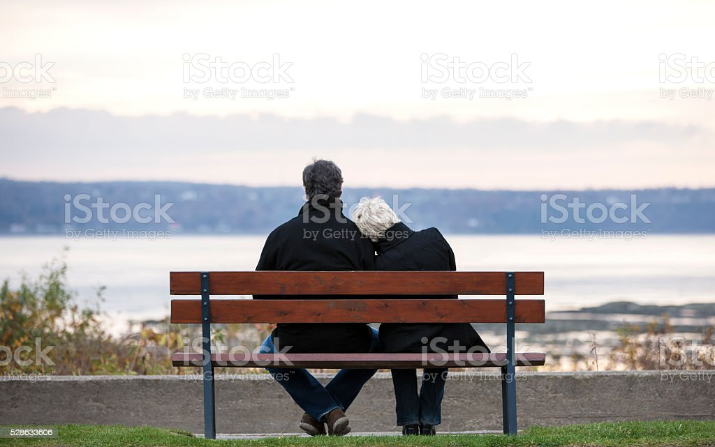 Mature couple sitting on park bench overlooking river. stock photo