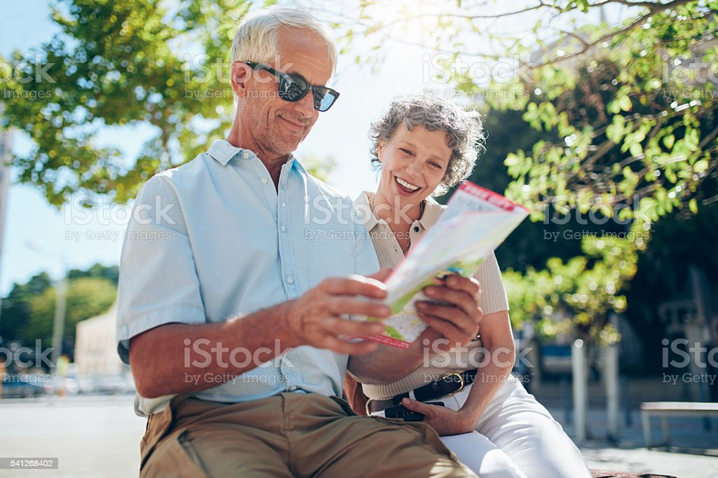 Mature couple sitting outdoors with a city map stock photo
