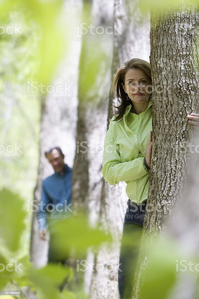 Mature couple standing behind trees stock photo