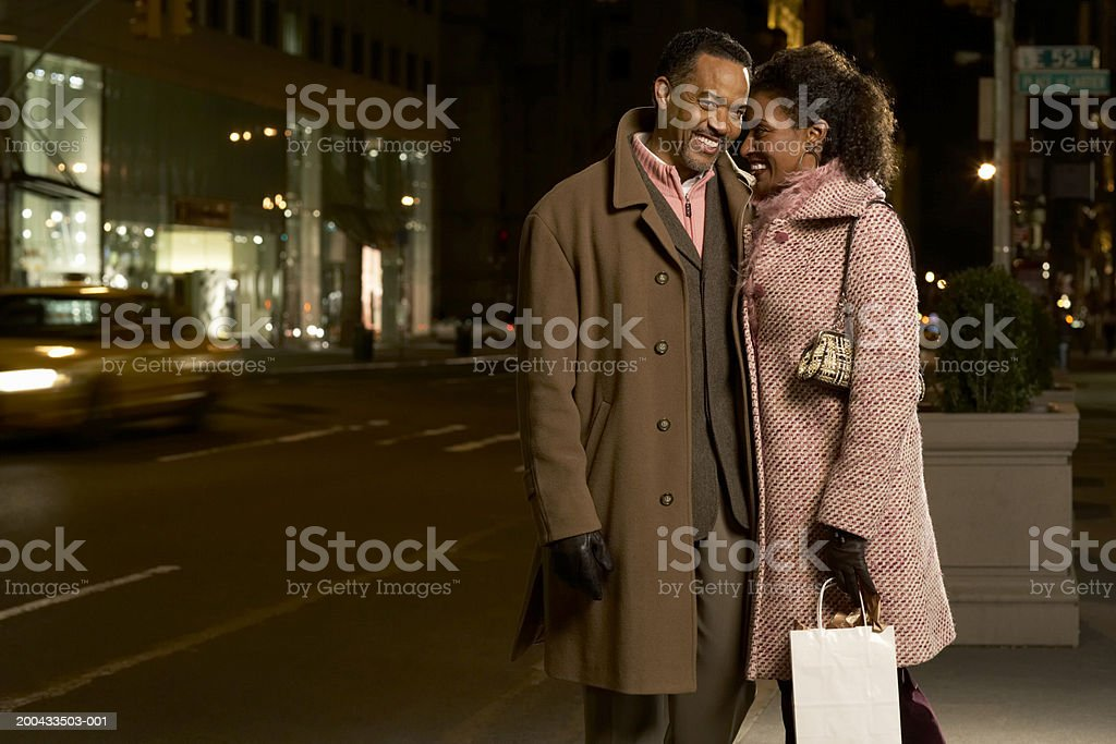 Mature couple standing on street, heads together, smiling, night royalty-free stock photo