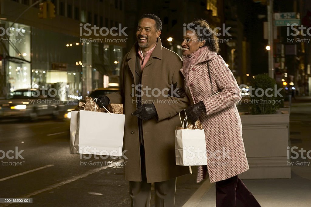 Mature couple standing on street holding shopping bags, smiling, night royalty-free stock photo