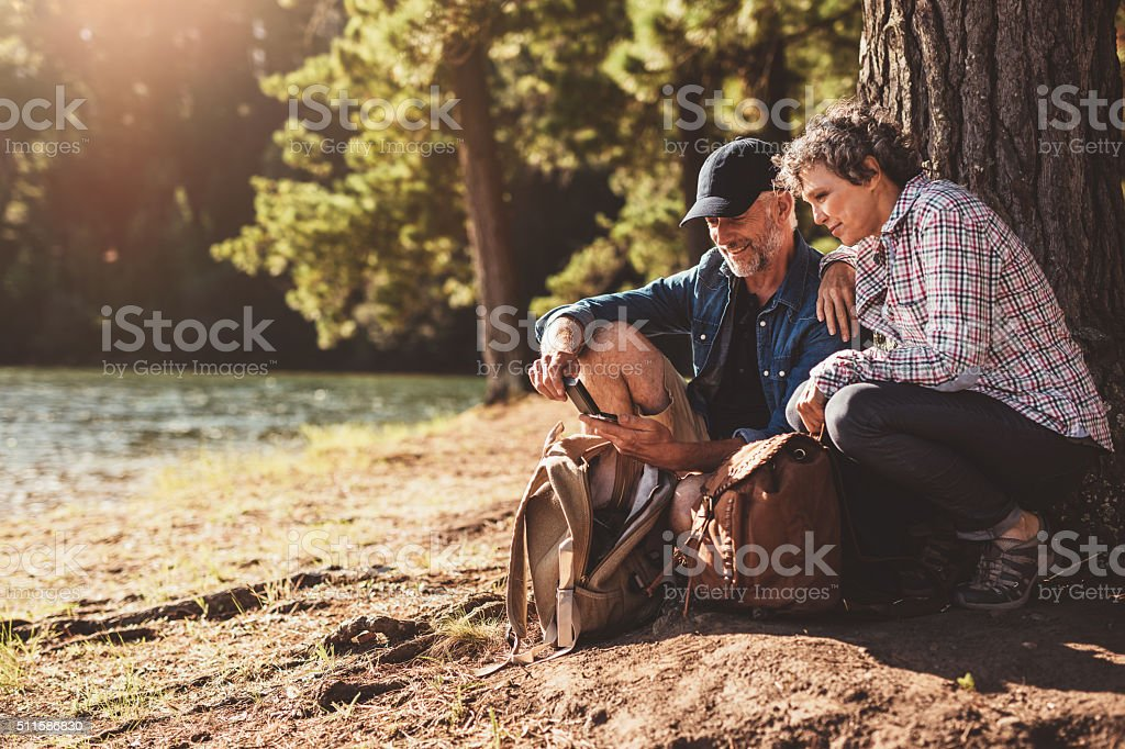 Mature couple stops to check their position while hiking stock photo