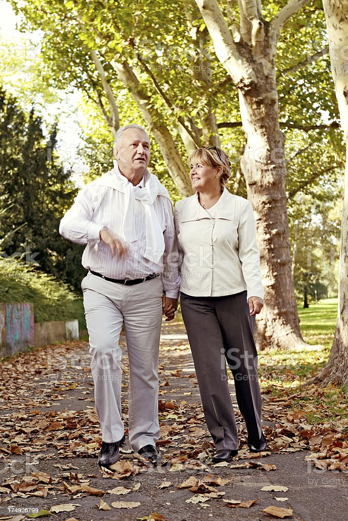 Mature couple taking an autumn walk in a park royalty-free stock photo