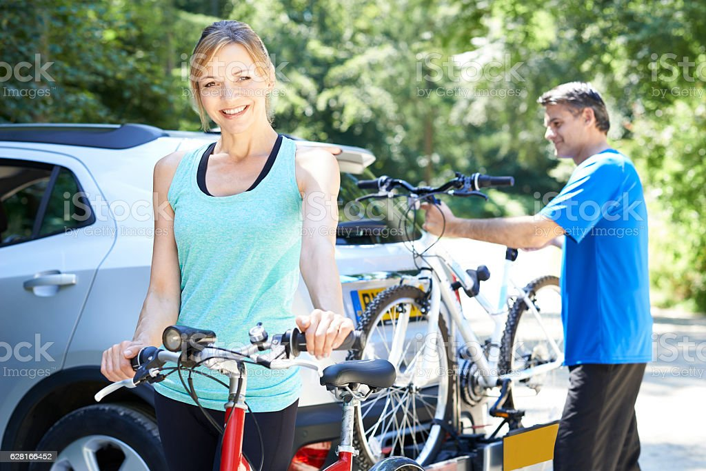Mature Couple Taking Mountain Bikes From Rack On Car stock photo
