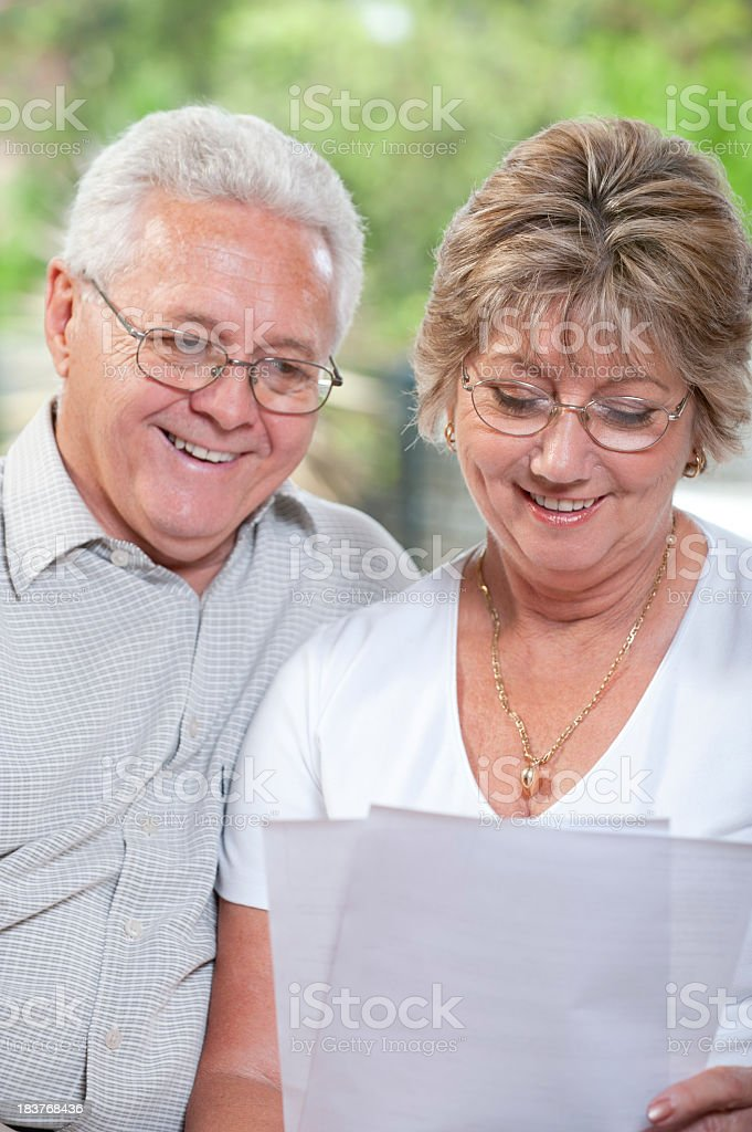 Mature couple talking  and smiling looking at document royalty-free stock photo