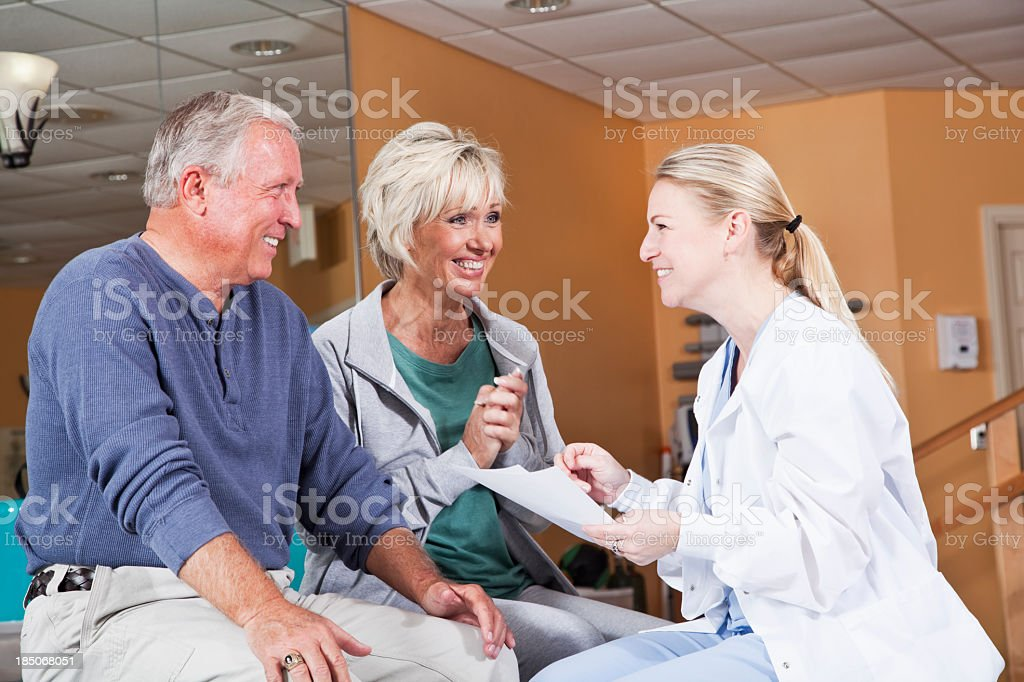 Mature couple talking with doctor stock photo