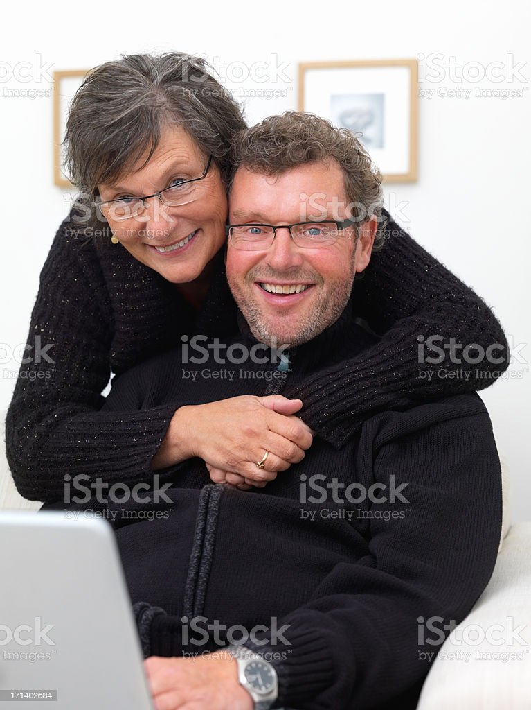 Mature couple together at home using laptop royalty-free stock photo