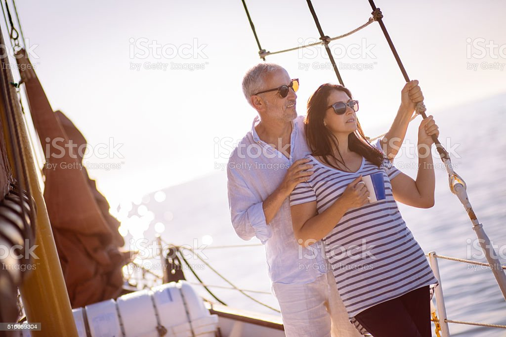 Mature couple travelling on a yacht with early morning coffee stock photo