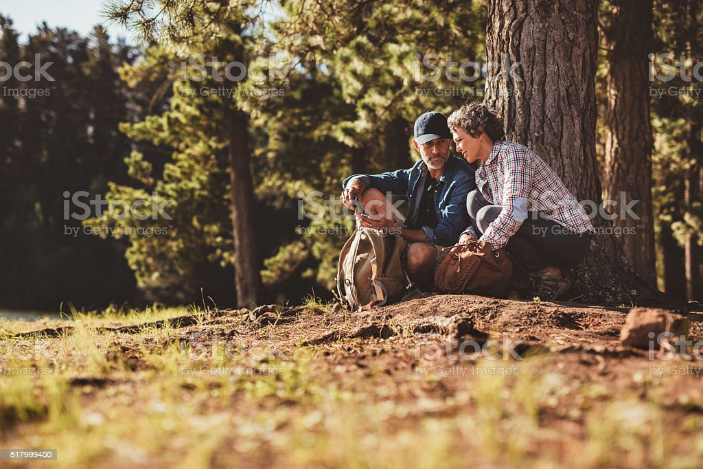 Mature couple using a compass on a hike stock photo