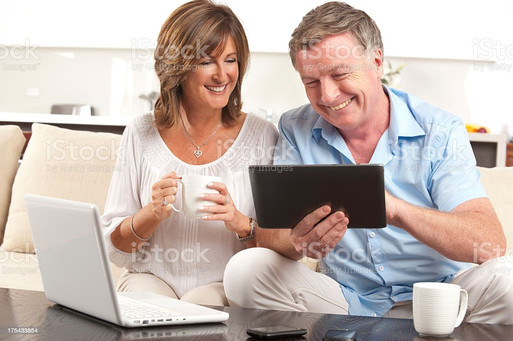 Mature couple using a digital tablet and laptop royalty-free stock photo