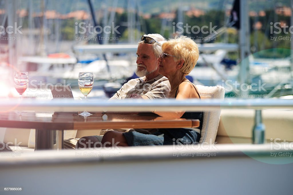 Mature couple using digital tablet on a yacht stock photo