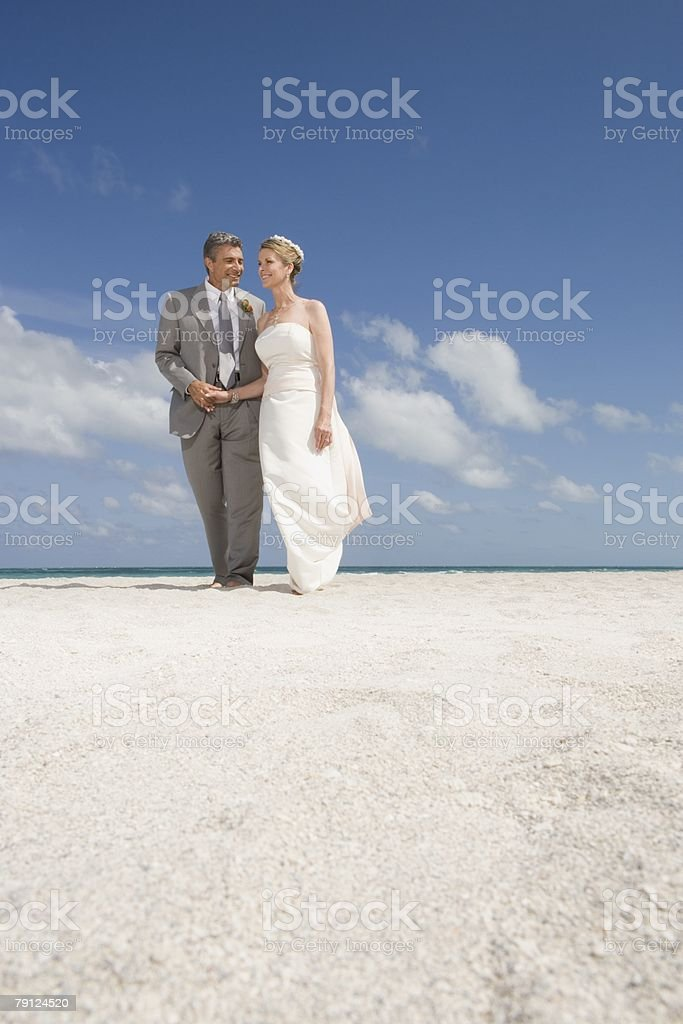Mature couple walking along the beach royalty-free stock photo