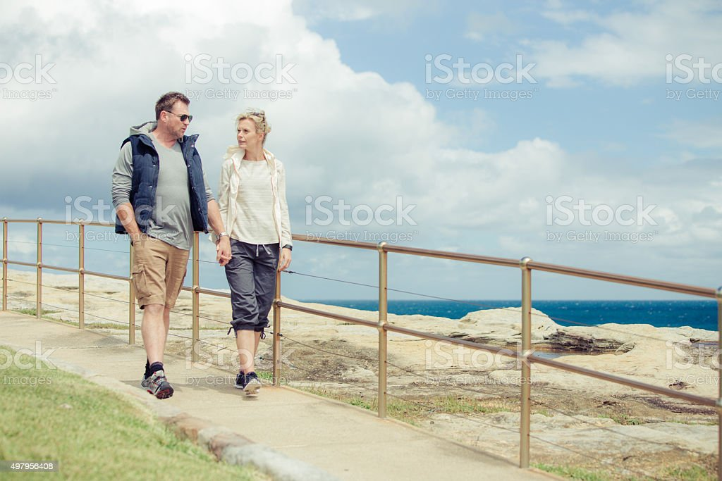 Mature couple walking along the coast stock photo