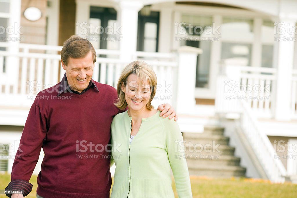 Mature couple walking in front of their house stock photo