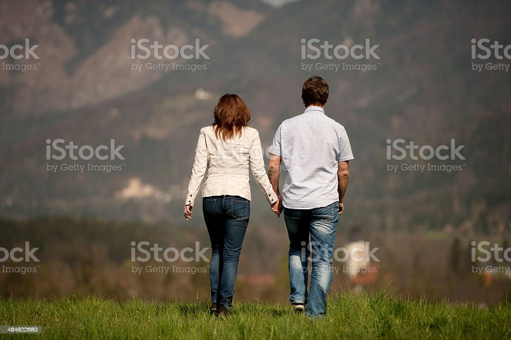 Mature couple walking on a meadow stock photo