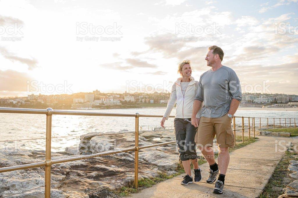 Mature couple walking on boardwalk at sunset, Bondi Beach stock photo