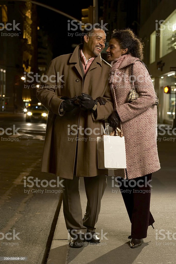 Mature couple walking on pavement, arms linked, smiling, night royalty-free stock photo
