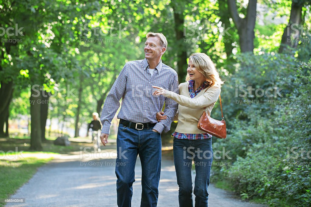 Mature couple walking together in a park stock photo