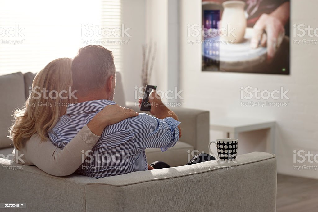 Mature couple watching television in living room stock photo