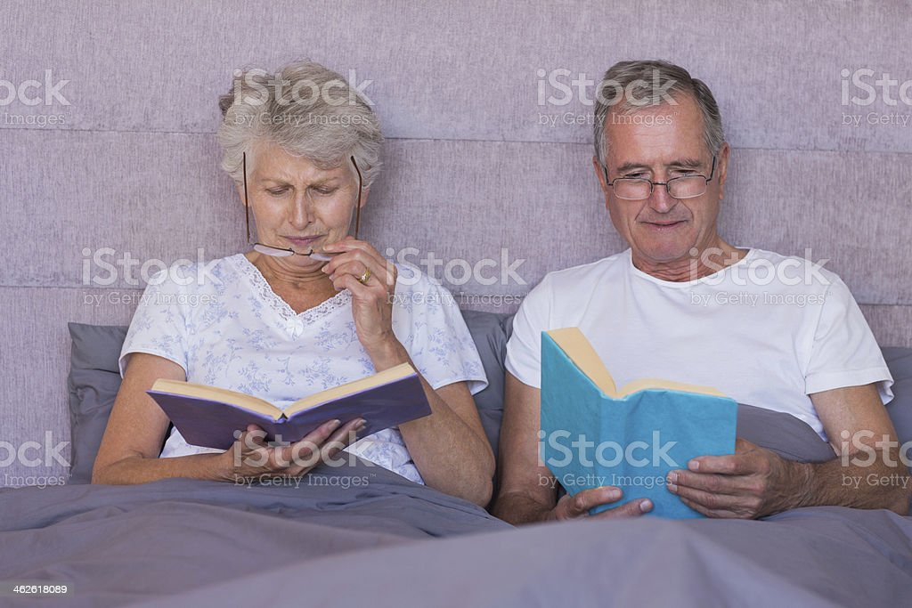Mature couple wearing glasses for reading books royalty-free stock photo