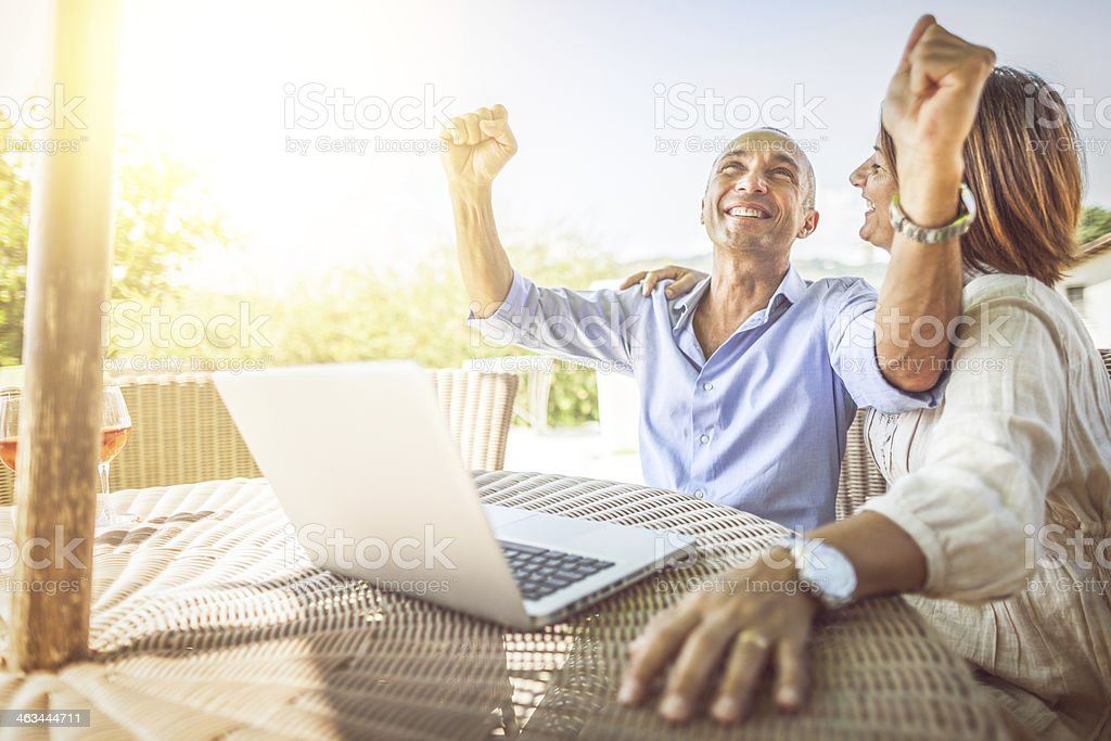 Mature couple winning on laptop stock photo