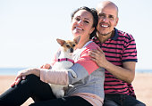 Mature couple with a small dog outdoors