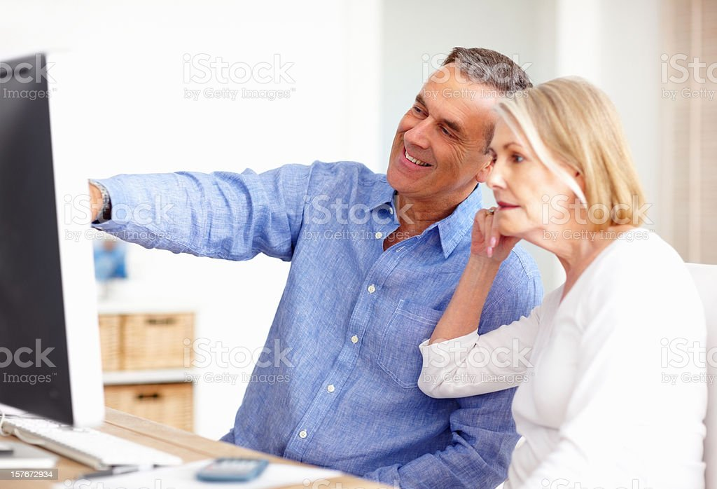 Mature couple with a smiling man pointing at computer screen stock photo