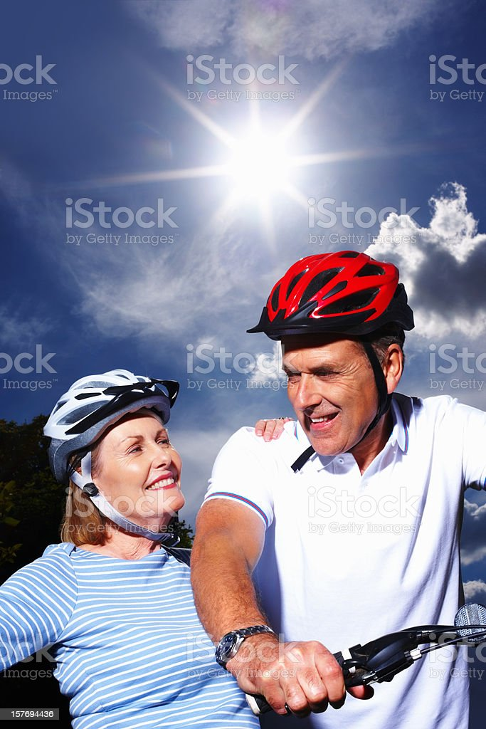 Mature couple with bicycle and protective helmet on sunny day royalty-free stock photo