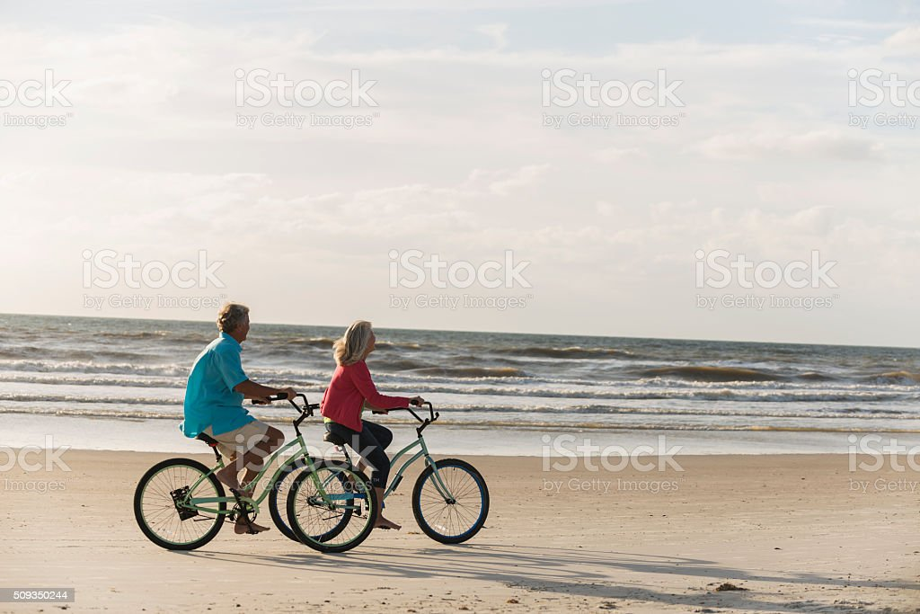 Mature couple with bicycles at the beach stock photo