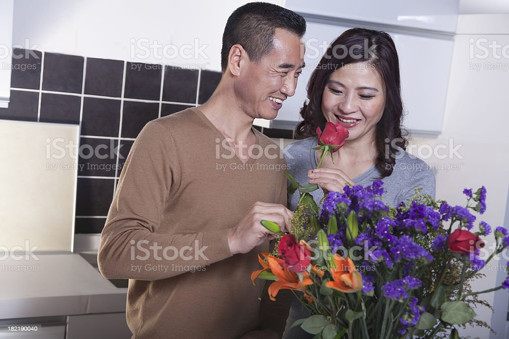 Mature Couple with Bouquet of Flowers, Man Holding a Rose royalty-free stock photo