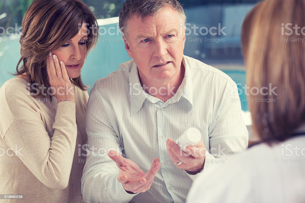 Mature couple with doctor and medicine stock photo