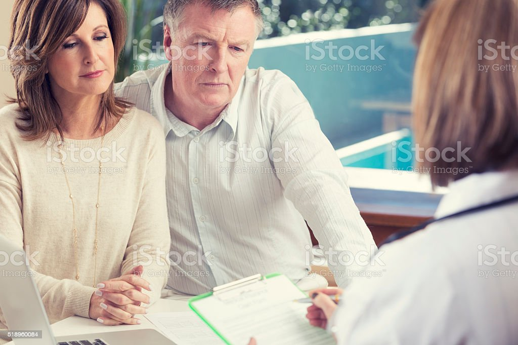 Mature couple with doctor. stock photo