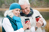 Mature couple with flasks of drink