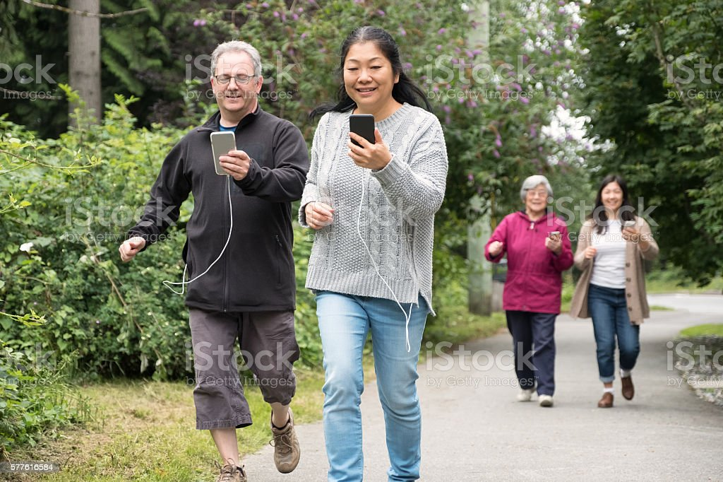 Mature Couple with Smartphones Run While Playing Augmented Reality Game stock photo