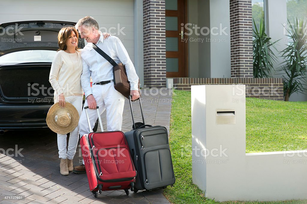 Mature couple with suitcases and car royalty-free stock photo
