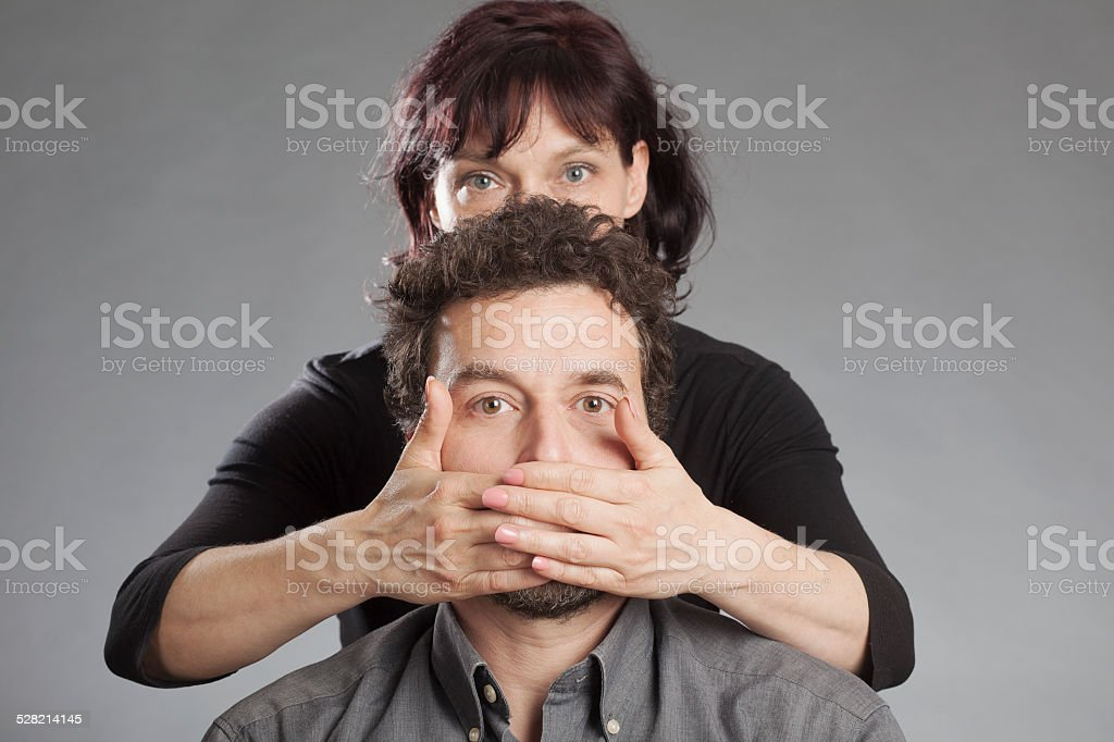 Mature couple woman covering man's mouth stock photo