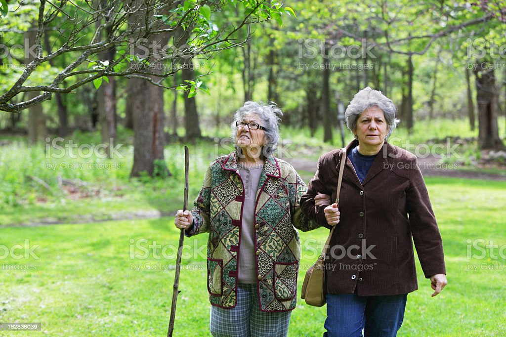 Mature Daughter and Senior Mother Walking at Nature Park royalty-free stock photo