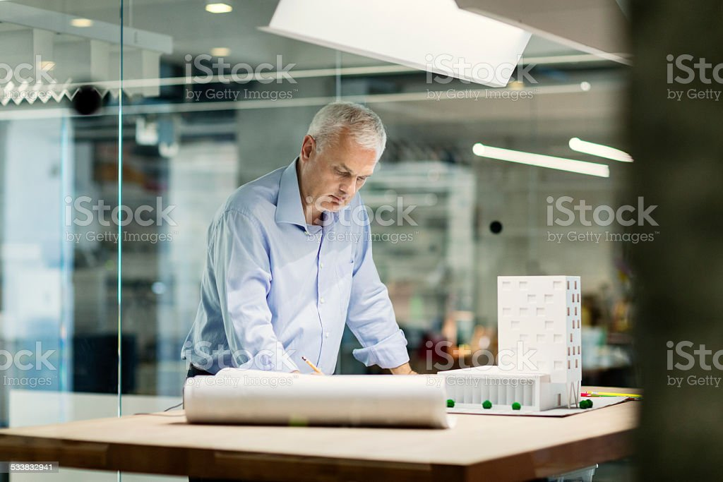Mature Designer working in his office. stock photo
