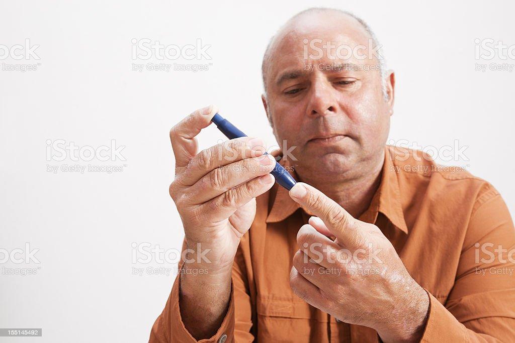 Mature diabetic man checking his blood sugar stock photo