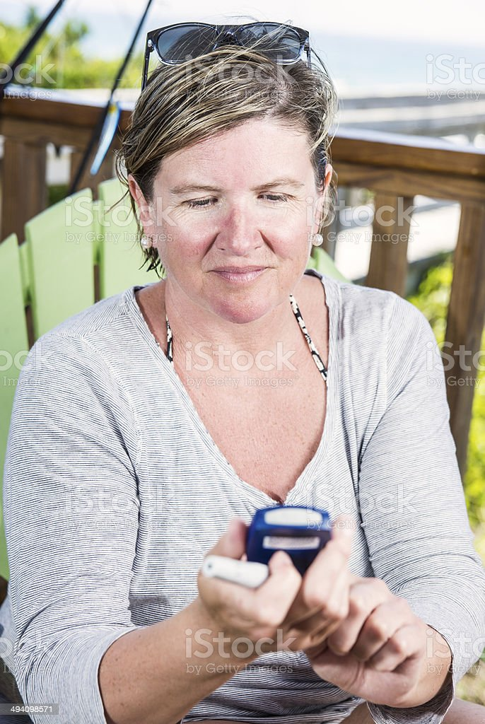 Mature diabetic woman checking her blood sugar royalty-free stock photo