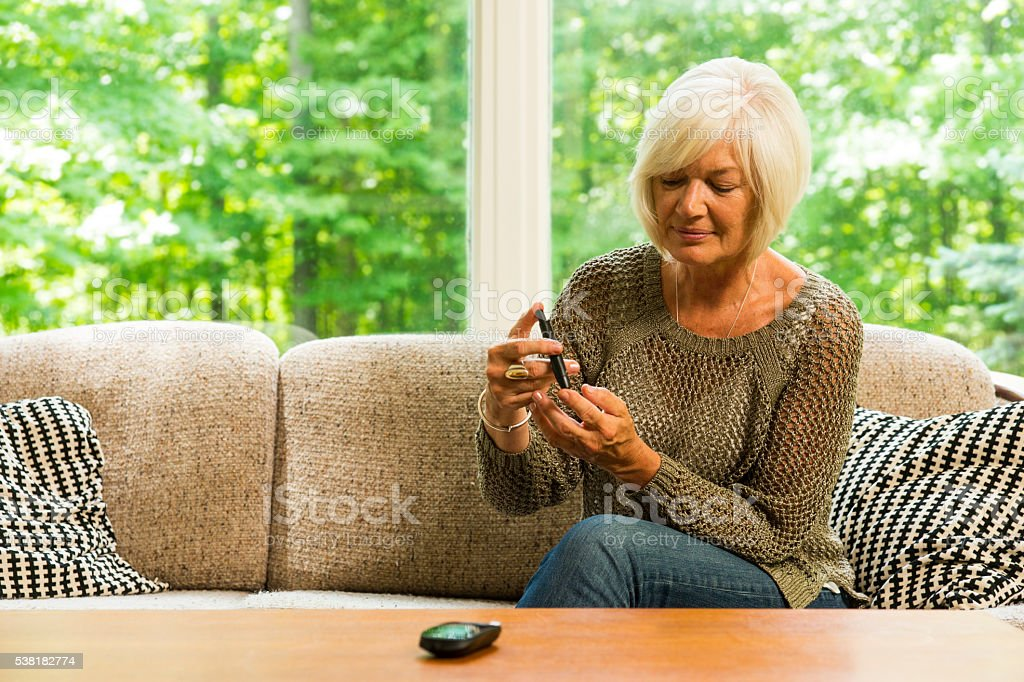 Mature diabetic woman checking her blood sugar stock photo