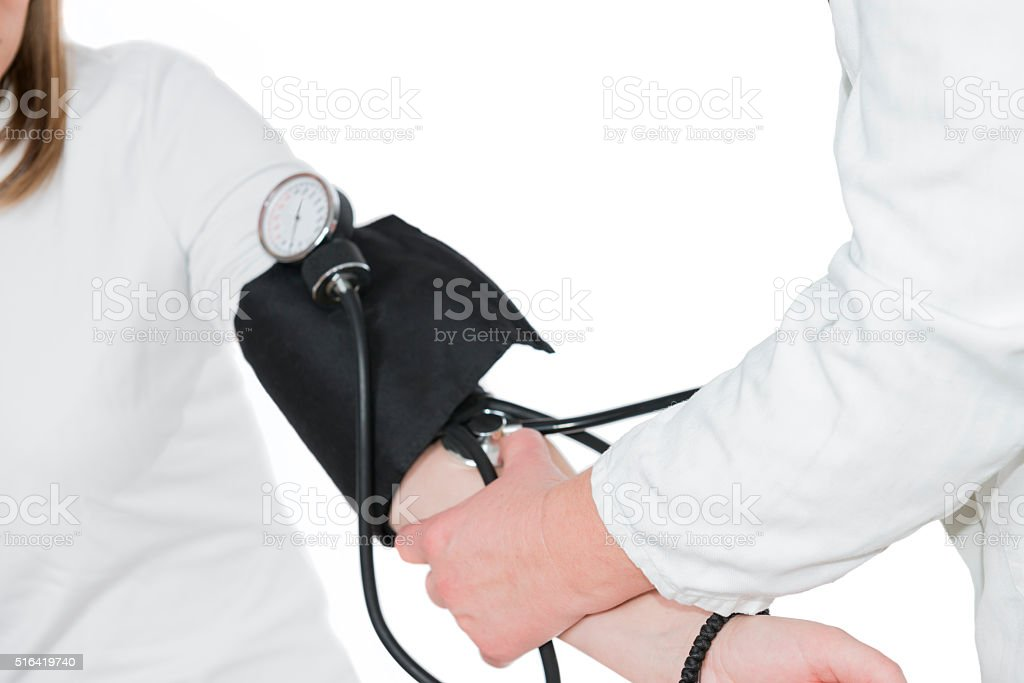 Mature Doctor Checking Young Patient Blood Pressure stock photo