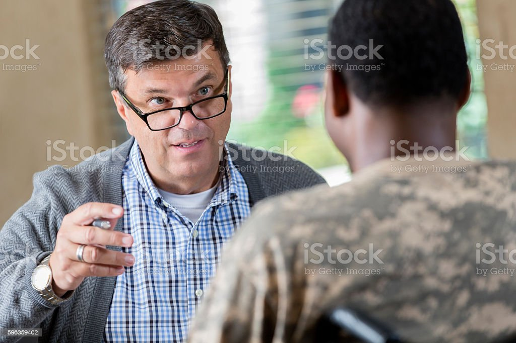 Mature doctor counseling young soldier during therapy session stock photo